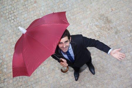 Businessman with umbrella checking if it's raining
