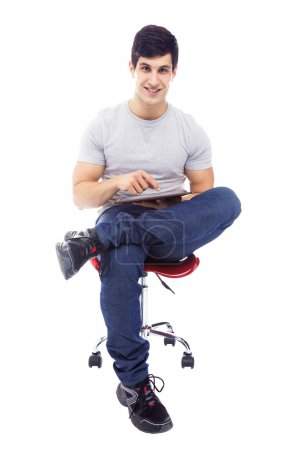 Smiling handsome latin man using a tablet computer, isolated ove