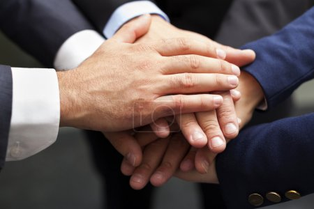 Businesspeople hands on top of each other as symbol of their union