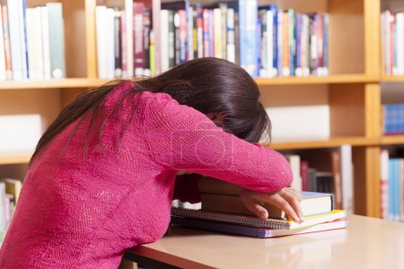 Tired student girl sleeping on the table at the library