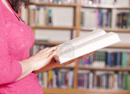 Closeup of female student reading a book in a library
