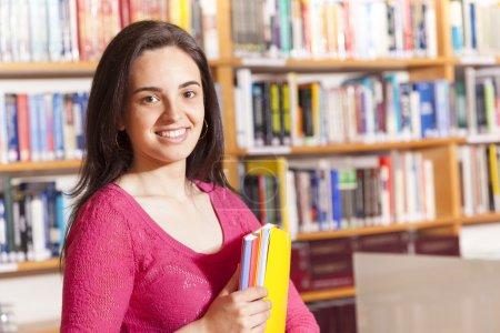 Photo pour Heureuse étudiante tenant des livres à la bibliothèque - image libre de droit
