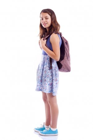School girl standing with backpack against white background