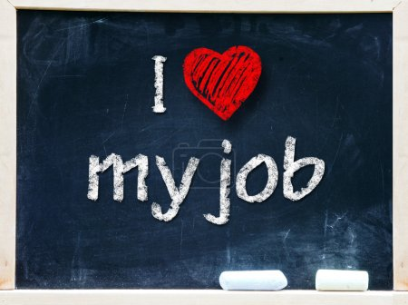 I love my job handwritten with white chalk on a blackboard.
