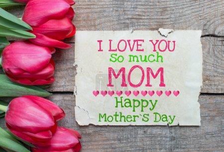 Photo pour Tulipes et papier avec texte Bonne fête des mères, je t'aime tellement maman sur une table en bois - image libre de droit