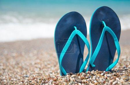 Blue flip flops on beach