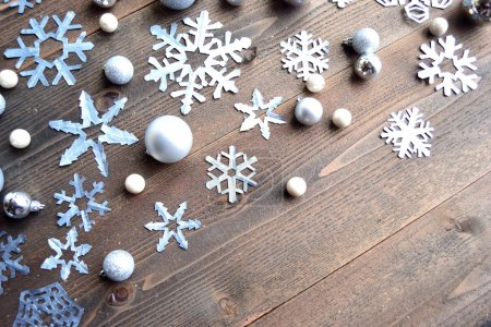 Paper cutout of snowflakes on wood background