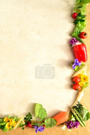 Frame of colorful vegetables with spring flowers