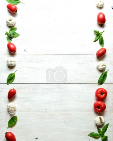 Tomato,garlic and basil leaf on white wood background