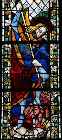 Photo pour Saint Michel piétinant Satan sur un vitrail dans la cathédrale de Rouen, France, le 10 février 2013. Cette fenêtre a été créée il y a plus de 500 ans, aucune libération de propriété n'est requise . - image libre de droit