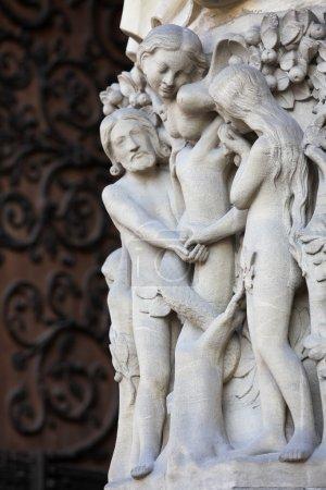 Photo pour Adam et Eve mangent le fruit défendu à l'arbre de vie au paradis, sculpté à la cathédrale Notre-Dame de Paris, en France. Ces statues ont été créées il y a plus de 500 ans, aucune libération de propriété n'est requise . - image libre de droit