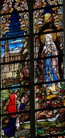 Photo pour Vitrail représentant l'apparition de Marie à Lourdes, pour Sainte Bernadette. Cette fenêtre a été créée il y a plus de 100 ans, aucune libération de propriété n'est requise . - image libre de droit