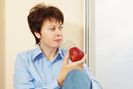 Woman with an apple sits next to the window