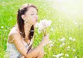 Girl on field with dandelion