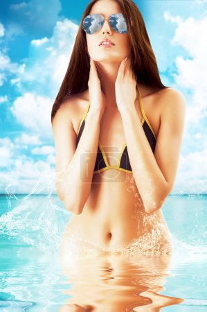 attractive brunette woman in sunglasses on the beach in water