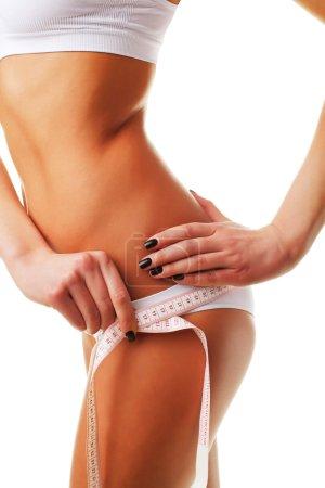 Photo pour Femme mesurant son corps sur fond blanc - image libre de droit