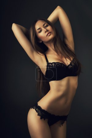 Photo for Sexy woman in black lingerie with raised hands on dark background - Royalty Free Image