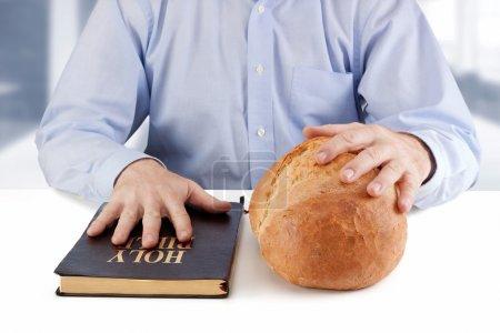 Photo pour Un homme tenant une Bible et du pain sur la table - image libre de droit