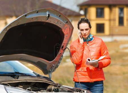 Photo for Woman at broken car with open hood call  service for help - Royalty Free Image