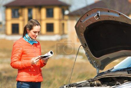 Photo pour Fille regarde dans le manuel de l'utilisateur dans le capot de voiture cassé ouvert - image libre de droit