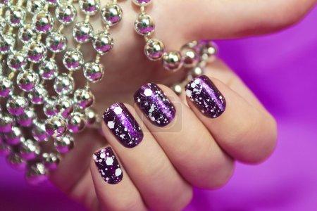 Photo pour Manucure de neige avec la conception de la chapelure blanc sur violet vernis brillant pour les ongles. - image libre de droit