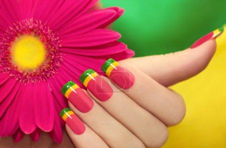 Photo pour Manucure multicolore avec laque rose, jaune et vert sur fond avec gerberas. - image libre de droit