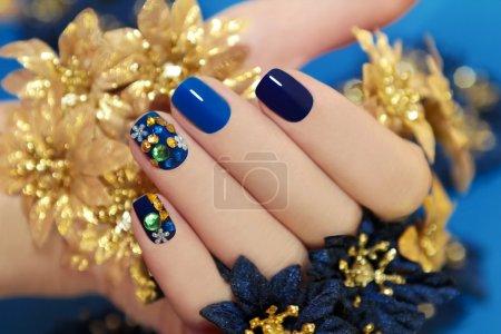 Photo pour Clous de femmes recouvert de laque bleu différentes nuances avec strass et fleurs à la main. - image libre de droit