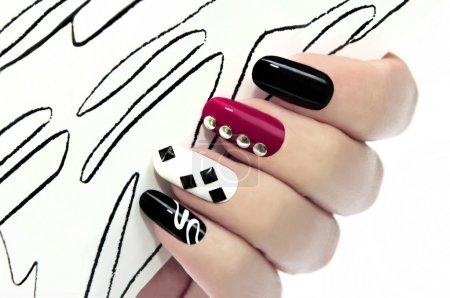 Photo pour Graphique manucure avec vernis noir, Bordeaux, blanc et ornements décoratifs sur les ongles. - image libre de droit
