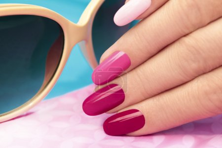 Photo for Pink manicure covered different in tone nail Polish on oval shaped nails. - Royalty Free Image