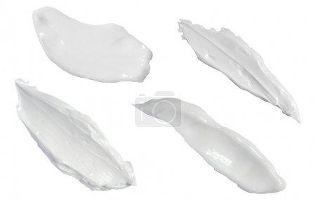 Photo pour Collection de différents traits d'une crème de beauté blanche sur fond blanc. chacun est tiré séparément - image libre de droit
