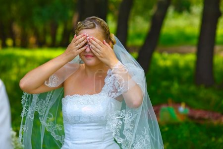 bride woman has closed eyes with his hands for surprise, mystery