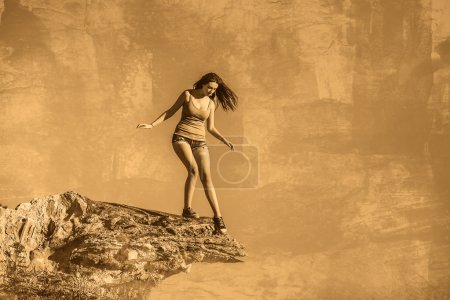 Photo for Acrophobia woman tall stands on top of a rock cliff edge and is fearful horror - Royalty Free Image