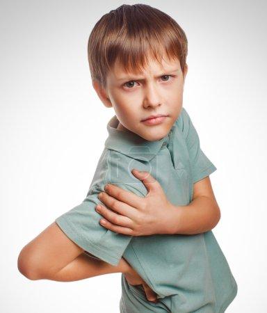 Osteochondrosis kid teenage boy isolatd holds his hand behind hi