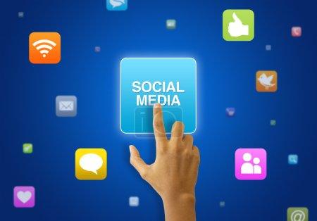 Photo pour Une personne touchant une icône des médias sociaux sur fond bleu . - image libre de droit