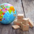 Miniature globe and boxes on wooden background...
