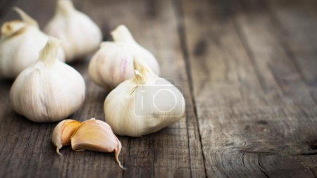 Several fresh garlic cloves on wood background....