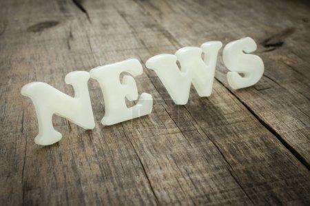 Photo pour Nouvelles de lettres en plastique sur fond bois - image libre de droit