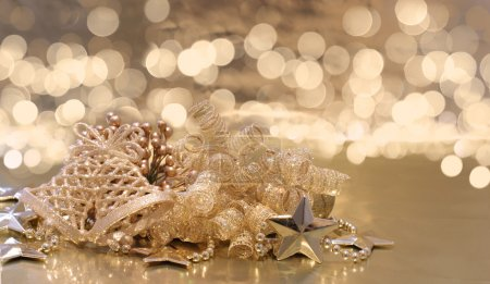 Photo for Christmas background of golden decorations on a background of defocussed lights - Royalty Free Image