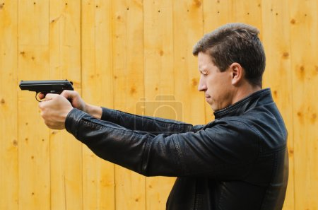 The man shoots from a pistol, having closed eyes
