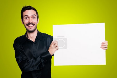 Smiling man holding blank white board on yellow backgroud