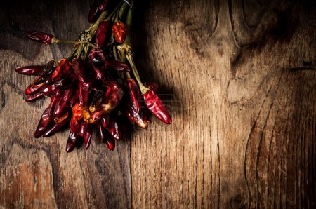 Photo for Dried hot red chilies on brown textured wood - Royalty Free Image