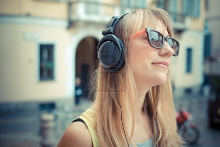 Photo for Beautiful blonde woman listening to music in the city - Royalty Free Image