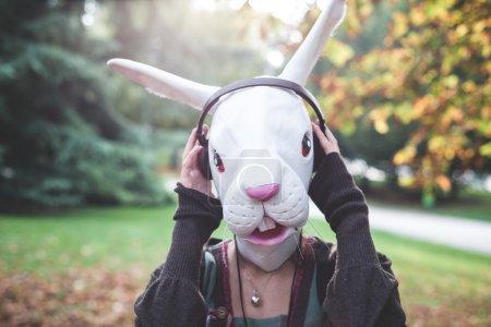 Rabbit mask woman listening to music