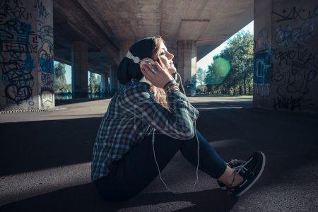 Photo pour Belle hipster blonde jeune femme écoute la musique dans le paysage urbain - image libre de droit