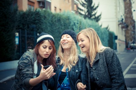 Photo for Three friends woman on the phone in the street - Royalty Free Image
