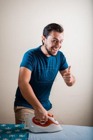 Photo pour Jeune homme élégant femme au foyer repassage à la maison - image libre de droit