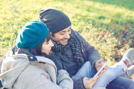 couple in love using tablet at the park