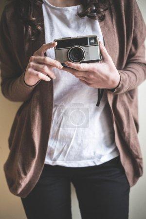 Photo pour Gros plan de mains femme avec vieille caméra à la maison - image libre de droit