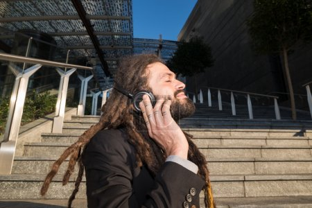 Stylish elegant dreadlocks businessman listening music