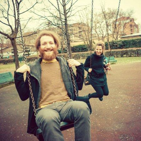 Foto de Joven pareja con estilo moderno jugando oscilaciones al aire libre - Imagen libre de derechos